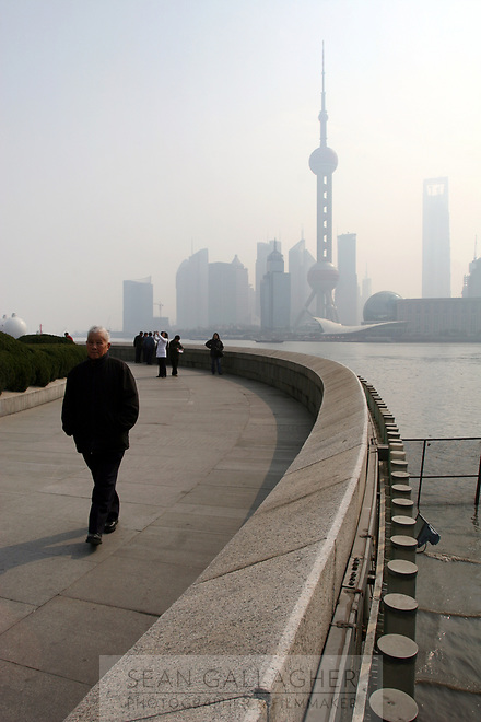 CHINA. Shanghai. A man walking on the Bund with the famous PuDong skyline behing him. Shanghai is a sprawling metropolis or 15 million people situated in south-east China. It is regarded as the country's showcase in development and modernity in modern China. This rapid development and modernization, never seen before on such a scale has however spawned countless environmental and social problems. 2008
