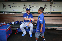 OAKLAND, CA - JULY 23:  Danny Valencia #23 of the Toronto Blue Jays talks to a young fan in the dugout before the game against the Oakland Athletics at O.co Coliseum on Thursday, July 23, 2015 in Oakland, California. Photo by Brad Mangin
