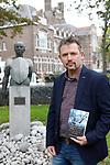 Foto: VidiPhoto<br /> <br /> KAMPEN – Historisch journalist/schrijver Herman Broers met zijn boek over dr. Willem Kolff voor het standbeeld van deze wereldberoemde Kampense arts. Op de achtergrond het voormalige ziekenhuis van Kampen waar Kolff jarenlang werkte.