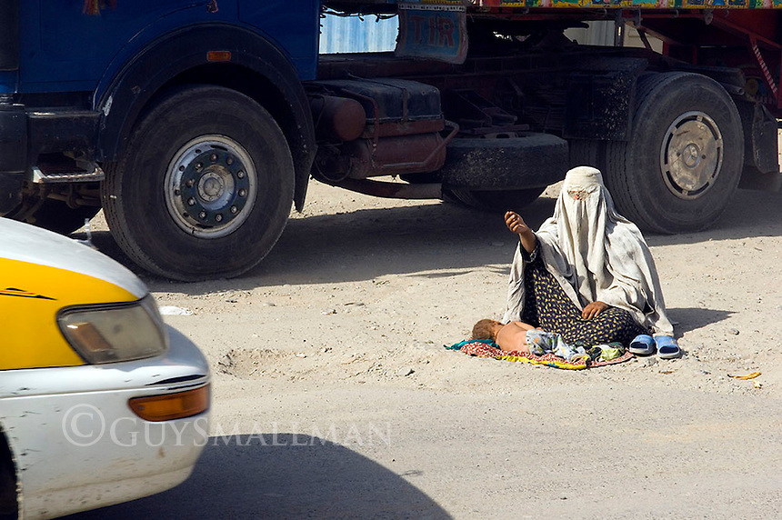 Street scene in Kabul Afghanistan. A woman begs from passing mtorists on the entrance to an industrial estate.