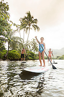 A young girl enjoys a family SUP lesson on the Wailua River, Kaua'i.