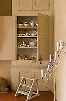 A cupboard in a corner of the kitchen has doors salvaged from a school and contains a collection of creamware and other porcelain