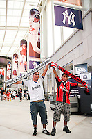 A Real Madrid fan poses for a photo with a A. C. Milan fan in Yankee Stadium prior a 2012 Herbalife World Football Challenge match at Yankee Stadium in New York, NY, on August 8, 2012.