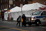 Pedestrians pass a triage tent at Maimonides Medical Center on March 28, 2020 in Brooklyn, NY.  NYC's daily death toll from the coronavirus nearly tripled from the previous 24-hour period from 85 on Friday to 222 on Saturday.  Photograph by Michael Nagle/Redux