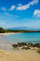 People enjoying Hapuna Beach, along the Big Island's Kohala Coast. This white sand beach has been rated one of the best beaches in the world. Hualalai mountain is seen in the distance.