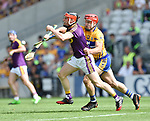 Diarmuid O Keeffe of Wexford in action against John Conlon of Clare during their All-Ireland quarter final at Pairc Ui Chaoimh. Photograph by John Kelly.