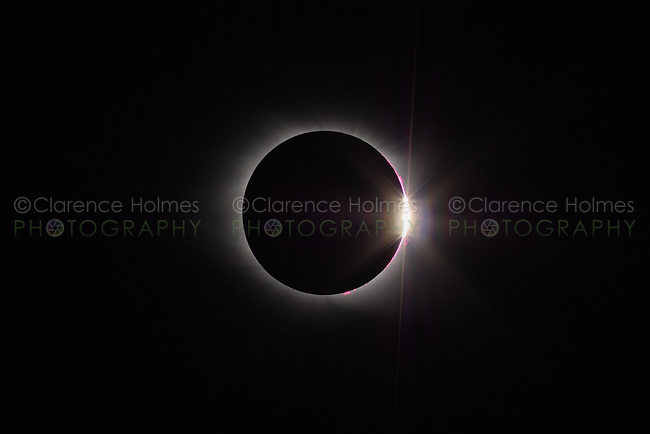 The Sun's corona and  the diamond ring effect are visible at the end of the total eclipse phase of the Great American Eclipse on August 21, 2017.  Pinkish solar flares are also visible near the Sun's surface.