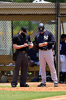 FCL Yankees manager Tyson Blaser (50) makes lineup changes with umpire Nelson Fraley during a game against the FCL Tigers on June 28, 2021 at Tigertown in Lakeland, Florida.  (Mike Janes/Four Seam Images)