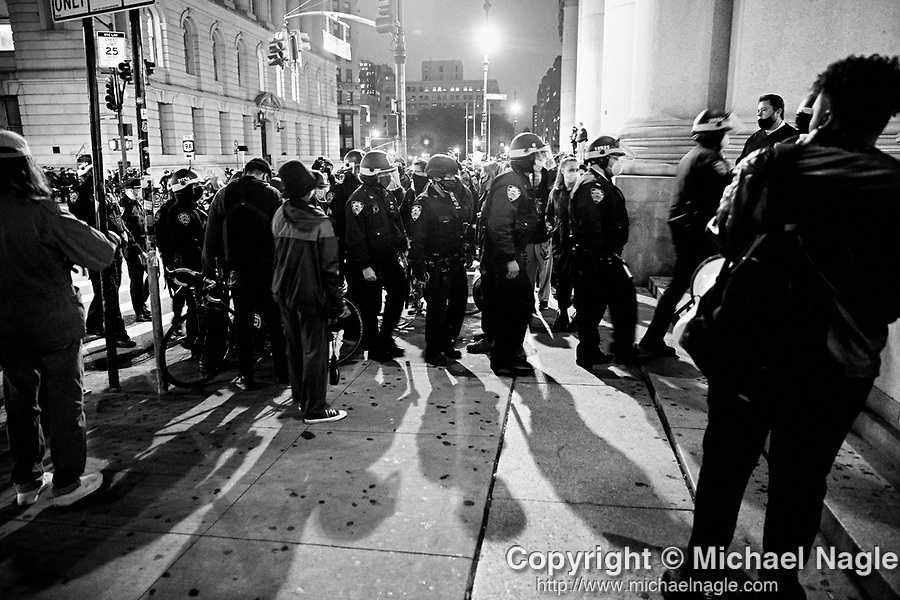 NEW YORK, NY — OCTOBER 27, 2020:  NYPD police officers march through a group of demonstrators protesting against police brutality, in response to the shooting of Walter Wallace Jr. by Philadelphia police officers the prior day, across from City Hall on October 27, 2020 in New York City.  The confrontation, recorded on a now viral video posted to social media, shows Wallace, a 27 year-old Black man who family members said was in the midst of a mental health crisis, holding a knife as two police officers shot and killed him.  Photograph by Michael Nagle