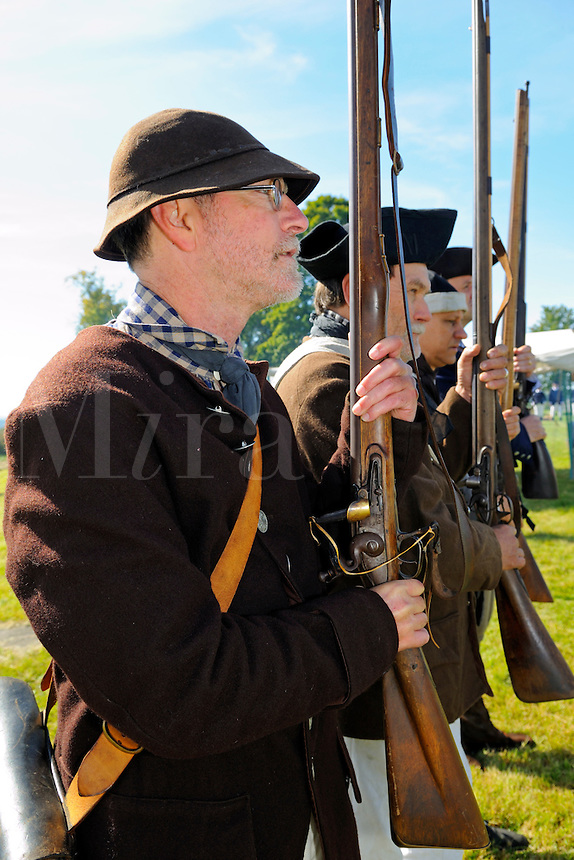 Ordinary colonial citizens, lightly armed and trained, organized as militia units for state defense, fought alongside regular soldiers of the Continental Army, practice drill at a Revolutionary War encampment on Bemis Heights, site of a major British defeat in October 1777, Saratoga National Historical Park, Stillwater, New York, USA..