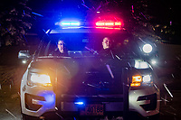 UAA University Police Department officers John Chu, right, and Kevin Stevenson, left, simulate responding to a call on Cuddy Quad.