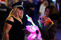 A woman wearing a police hat  in Wind Street, Swansea, Wales  on Mad Friday, Booze Black Friday or Black Eye Friday, the last Friday night before Christmas Day, when traditionally people in the UK go out to celebrate the start of their holidays. Friday 22 December 2017