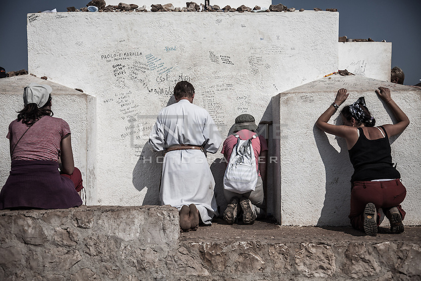 Pilgrims absorbed in prayer at the  cross on top of the Mt. Krizevac.<br /> Medjugorje, Bosnia and Herzegovina. July 2012