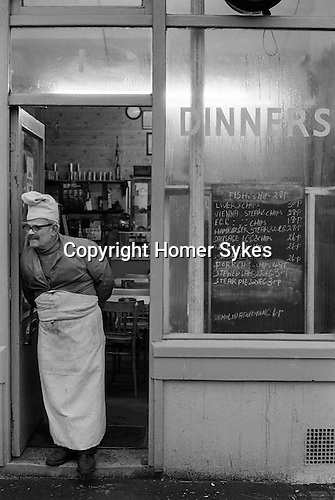 Whitechapel, London. 1974<br /> The proprietor in chefs hat and apron, buttoned up to his jacket, stands outside his greasy spoon Dinners café in Brick Lane waiting for lunchtime customers. The blackboard dinner menu is almost everything with chips. Fish & chips 27p, Liver & chips 30p, Vienna steak & chips 28p, Egg & chips 18p, Hamburger steak & 2 veg 28p, Sausage egg & chips 26p, <br /> 2 egg & chips 26p, 2 sausage & chips 26p, Pork chop & chips 45p, Stewed lamb & 2 veg 30p, Steak pie & 2 veg 30p, and finally for dessert Semolina pudding  will cost you 6p. The Vienna steak & chips, perhaps gives a clue to his nationality.