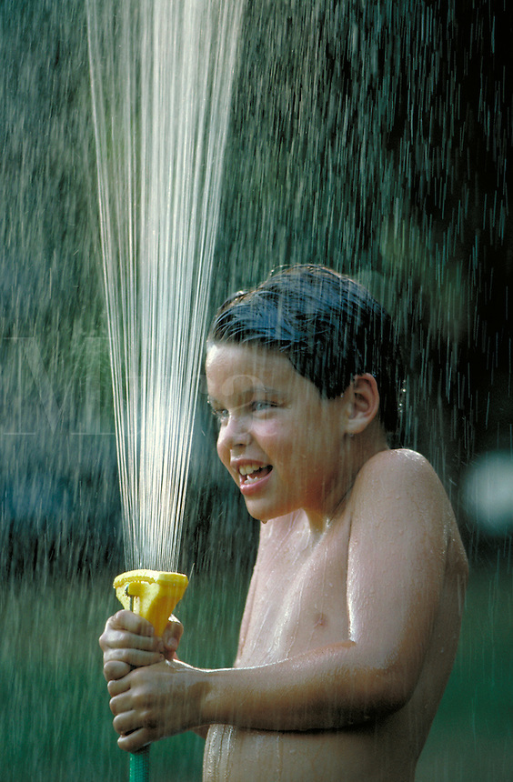 A twelve year old boy enjoys the spray from a water hose as he cools off during a hot summer afternoon. play, child, children. young boy with water hose. Georgia, backyard.