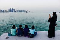 QATAR, Doha, skyscraper east bay, filipino migrant worker and veiled muslim woman on friday at sea front corniche / KATAR, Doha, Wolkenkratzer der Eastbay, philippinische Gastarbeiter und muslimische Frau am Freitag an der Corniche Seepromenade
