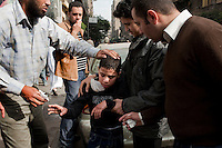 As protesters march through the streets of central Cairo amidst tear gas fired by the police, a child is helped as he suffers from the effects of the gas. Continued anti-government protests take place in Cairo calling for President Mubarak to stand down. After dissolving the government, Mubarak still refuses to step down from power.