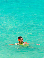 Woman wearing orchid flower lei and orange hibiscus in hair, playing in the blue ocean waters of Hawaii