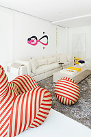 An artwork on the wall and a red striped Zingy chair by Gaetano Pesce bring accent colours to the predominately neutral palette of the living room.