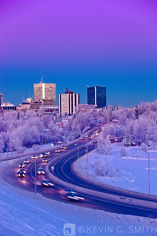 Alpenglow over the Anchorage skyline with the lights from rush hour traffic on Minesota blvd. in the foreground, winter, Southcentral Alaska, USA.