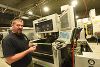 Guy Joubert with Wilson Combat gun makers shows Wednesday July 14 2021 one of several new machines added after a major expansion of the company south of Berryville. This machine makes pistol parts.<br />(NWA Democrat-Gazette/Flip Putthoff)