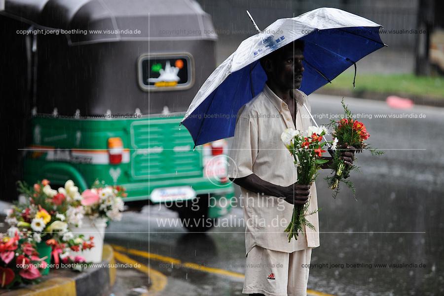 SRI LANKA, Colombo, man sells flower in rain / SRI LANKA, Colombo, Mann verkauft Blumen im Regen