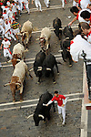 Participants run in front of Victoriano Cortes bulls during the bull run of the San Fermín Festival, on July 10, 2013, in Pamplona, northern Spain. © Pedro ARMESTRE