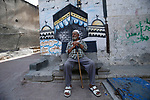 An elderly Palestinian man sits in front of a mural depicting the Kaaba, Islam's holiest shrine, in Gaza City on July 27, 2020. Photo by Osama Baba