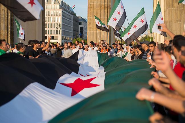 """Protest gegen den syrischen Diktator Bashar al-Assad.<br /> Am Freitag den 21. August 2015 protestierten mehrere hundert Menschen, die meissten Buergerkriegsfluechtlinge aus Syrien, gegen den fortdauernden Buergerkrieg in ihrem Herkunftsland. Sie gedachten annlaesslich des 2. Jahrestag der Opfer des Giftgas-Angriffs vom 21. August 2013 in Damaskus. Das Assad-Regime hatte ueber 1.600 Menschen mit dem Nervengift Sarin ermordet.<br /> Nach Angaben des deutschen Vertreters der """"Syrischen Nationalen Koalition"""", Dr Bassam Abdullah,  werden in Syrien weiterhin Menschen durch Giftgas durch die Regierungstruppen getoetet. Die Koalition ist ein Zusammenschluss von syrischen Muslimen, Christen, Assyrern und Kurden.<br /> Im Bild: Demonstranten mit einer ueberdimensionalen syrischen Flagge.<br /> 21.8.2015, Berlin<br /> Copyright: Christian-Ditsch.de<br /> [Inhaltsveraendernde Manipulation des Fotos nur nach ausdruecklicher Genehmigung des Fotografen. Vereinbarungen ueber Abtretung von Persoenlichkeitsrechten/Model Release der abgebildeten Person/Personen liegen nicht vor. NO MODEL RELEASE! Nur fuer Redaktionelle Zwecke. Don't publish without copyright Christian-Ditsch.de, Veroeffentlichung nur mit Fotografennennung, sowie gegen Honorar, MwSt. und Beleg. Konto: I N G - D i B a, IBAN DE58500105175400192269, BIC INGDDEFFXXX, Kontakt: post@christian-ditsch.de<br /> Bei der Bearbeitung der Dateiinformationen darf die Urheberkennzeichnung in den EXIF- und  IPTC-Daten nicht entfernt werden, diese sind in digitalen Medien nach §95c UrhG rechtlich geschuetzt. Der Urhebervermerk wird gemaess §13 UrhG verlangt.]"""