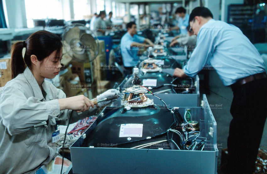 China. Province of Zhejiang. Hangzhou. Soyea is one company of the West Lake Electronics Group Co., Ltd.  Soyea produces television sets for the chinese market. A woman installs and spot-welds electronic components in a new TV set. She is a worker on an assembly line. © 2004 Didier Ruef