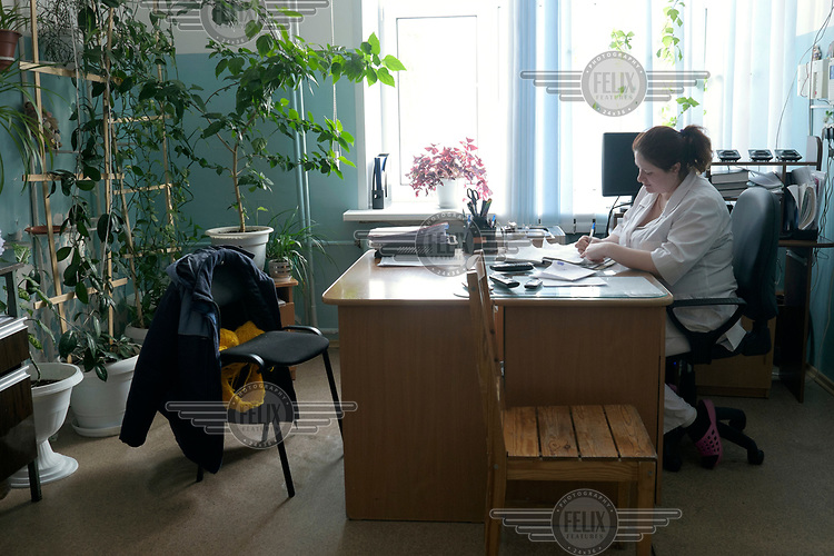 Paramedic Irina, completes paer work at her desk in Turukhansk hospital.