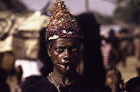 A man in a cap decorated with straw and textile grimaces during the War Dances - Half Graway, Maryland County, Liberia, 1979
