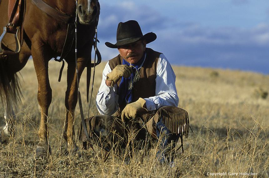 Cowboy kneeling in front of horse. Ponderosa Ranch. Senaca OR.