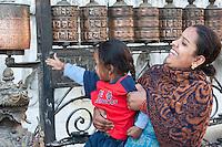 Kathmandu, Nepal.  Mother and Child Spinning Prayer Wheels at Swayambhunath Temple.
