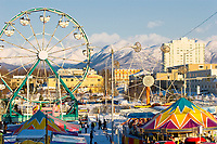 Carnival rides and mountain views at the Fur Rondy Festival, downtown Anchorage.