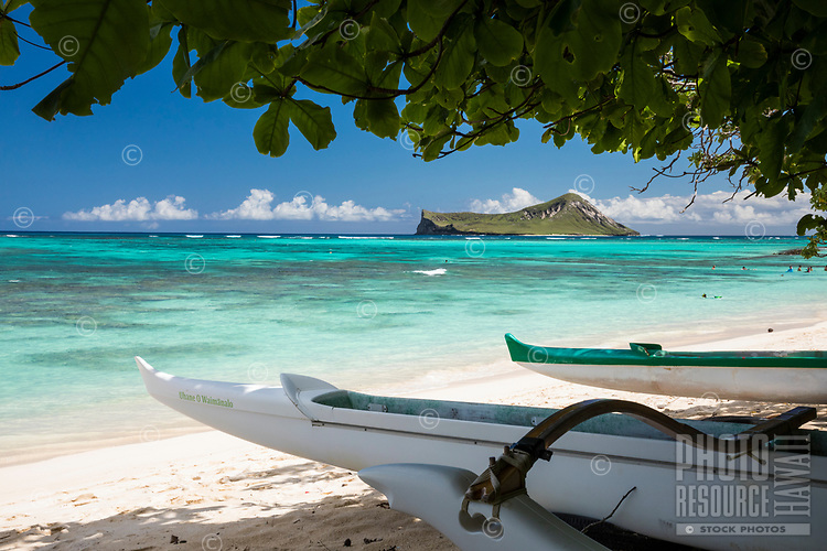 Outrigger canoes at Waimanalo Beach, Windward O'ahu; distant residents and visitors alike enjoy the beach and the reef of Waimanalo Bay, with Rabbit (or Manana) Island beyond.