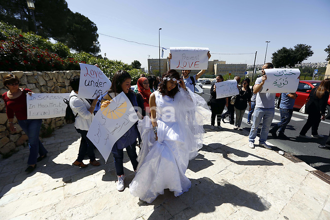 An Israeli Arab young woman wears a bridal gown as she plays the part of a bride without her groom as they pass the Rose Garden on their way to the Jerusalem offices of Israeli Prime Minister Benjamin Netanyahu, 14 April 2013. Israeli Arabs and Palestinians held the protest under the banner 'Love in the Time of Apartheid' to challenge Israeli laws and policies that prevent the reunification of families when one partner holds Israeli citizenship and the other is a resident of the 'occupied territories.' The protest passed without incident. Photo by Sliman Khader