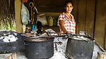 Rosita and a few pots in the open-air kitchen of her thatched roof cabin.  Behind her are shelves of kitchen supplies and the <br /> slat door to the cabin's one room, where they sleep.