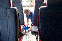 Premises staff cleaning out the minibus,  State Secondary Roman Catholic school.