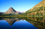 The glass smooth surface of Pray Lake with mountain reflections in Glacier National Park