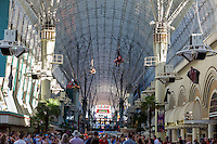 Las Vegas, Nevada.  Fremont Street.  Three Zoomline Riders Fly above the Crowds on the 1750-foot Zip Line.