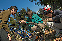Parents stop to help their son repair the flat tyre of his mountain bike.
