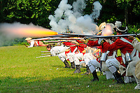 British redcoat soldiers of the Ninth Regiment of Foot fire a musket volley during a Revolutionary War reenactment at the Nathan Hale Homestead, Coventry, Connecticut, USA...