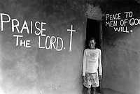 Uganda. West Nile. Adjumani.  A young boy wearing a Dallas Cowboys long-sleeved T-shirt stands alone by the door of a mud house. Various religious texts are written on both walls: Praise the Lord. Peace to men of good will. West Nile sub-region (previously known as West Nile Province and West Nile District) is a region in north-western Uganda. © 1989 Didier Ruef