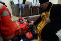 A orthodox priest blesses an inured Red Cross Medic in the makeshift clinic, a hotel lobby.  Kiev, Ukraine