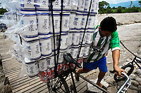 A smuggler pushes a bicycle loaded with contraband on the foot bridge across the river Tachira on the Colombia-Venezuela border, 2 May 2006. Venezuelan gasoline, being 20 times cheaper than in Colombia, is the most wanted smuggling item, followed by food and car parts, while reputable Colombian clothing flow to Venezuela. There are about 25,000 barrels of gasoline crossing illegally the Venezuelan border every day. The risky contraband smuggling, especially during the rainy season when the river rises, makes a living to hundreds of poor families in communities on both sides of the frontier.