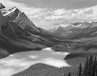 """""""Peyto Lake"""" <br /> Banff National Park; Alberta, Canada<br /> <br /> A short walk from the parking area leads to a popular overlook where this photograph was recorded. Shadows on the surface of Peyto Lake were articulated especially strongly on this day as a result of an abundance of finely ground rock in the water from glacial action nearby. A dark yellow filter was used to strengthen shadows, increase cloud texture and darken the blue sky. The Icefields Parkway can be seen in the valley below."""