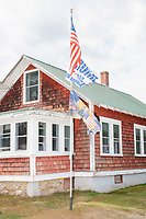 """A variety of Trump campaign flags are seen with an American flag in the front yard of Willard and Dolly Smith in Meredith, New Hampshire, on Thu., Sept. 24, 2020. Dolly Smith said that many people stop to take pictures of their display, which includes flags that say """"All Aboard the Trump Train,"""" """"Trump 2020 / Keep American Great,"""" """"Trump 2020 / No more bullshit,"""" """"Vote Republican / no Socialism,"""" and flags featuring Trump standing on a military tank and dressed as action hero John Rambo with a machine gun."""