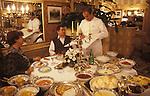 Paul Bocuse in Lyon France portrait signing menus in his restaurant. 1980s