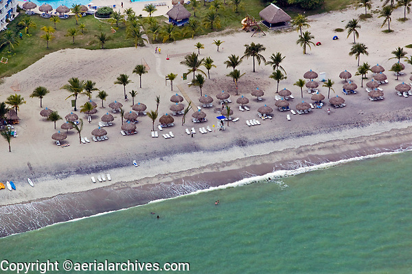 aerial photograph of straw umbrellas, reclining chairs and palm trees at Playa Blanca, a Pacific coast beach, Panama